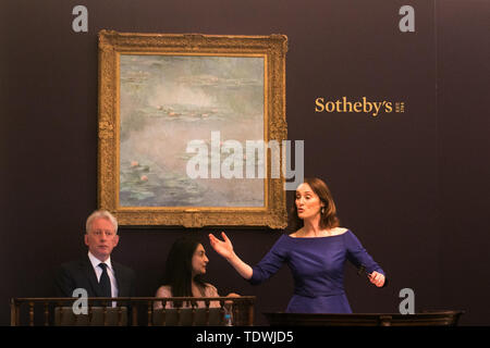 London UK. 19th June 2019. Auctioneer Helena Newman takes bids for 'Nymphéas ' by Claude Monet, oil on canvas, Estimate £25,000,000m  which sold at hammer for £21,000,000m  at the Impressionist & Modern Art Evening Auction  at Sotheby's London Credit: amer ghazzal/Alamy Live News - Stock Image
