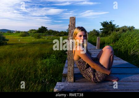 Attractive young woman in nature in sunset evening time sitting inclined on wooden post barefeet barefoot - Stock Image
