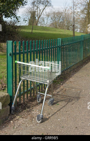 An ASDA shopping trolley abandoned some distance from the supermarket, near an entrance to Farnworth Central Park, - Stock Image