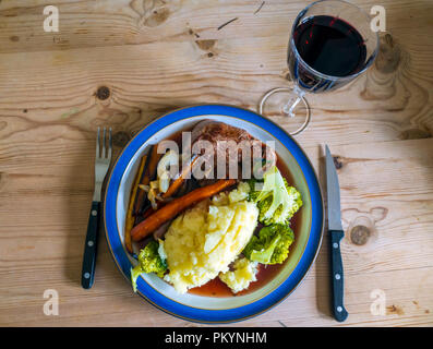 English dinner meal Beef Fillet steak with broccoli mashed potatoes  roasted carrots parsnips onions and gravy and a glass of red wine - Stock Image