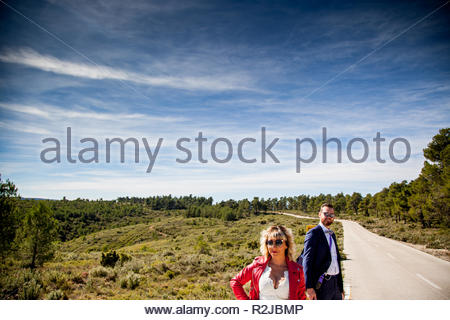 A woman dressed as a bride, with a red jacket waiting next to a man dressed in a suit on a lonely road. - Stock Image