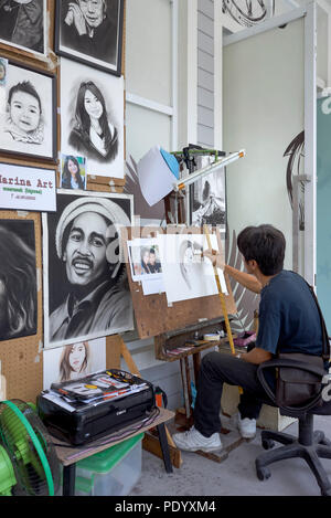 Artist at work in a studio painting portraits from a photograph. Thailand art studio - Stock Image