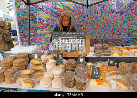 Woman selling various Portuguese local cheese round cheeses on food stall at LX Factory Market in Lisbon Lisboa Portugal  KATHY DEWITT - Stock Image