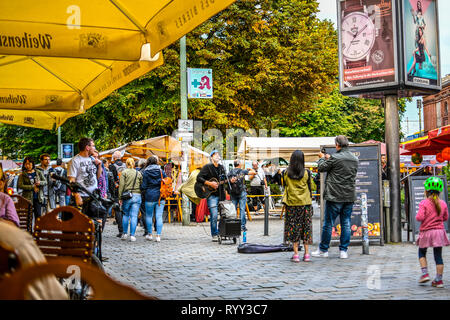 Tourists and local Germans enjoy a street performer singing and playing guitar in the outdoor Hackescher Markt square of Berlin Germany. - Stock Image