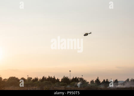 London, United Kingdom. 14 July 2018. PICTURED: Police helicopter provided aerial support. Fifteen fire engines and 97 firefighters and officers were called to a grass fire on Staines Road in Feltham. Grass land the size of four football pitches is alight. Smoke from the fire has travelled near to Heathrow airport but it is not affecting their operations. Fourteen horses were removed from a nearby field to a place of safety. Credit: Peter Manning/Alamy Live News - Stock Image