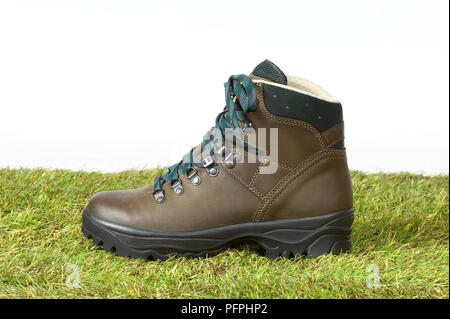 Brown hiking boot on grass, close-up - Stock Image