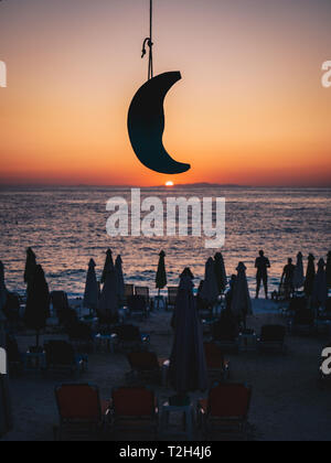 Beautifull sunrise in Thassos, Greece with the sun rising from the sea, tourists on the beach watching the sunrise and a model moon. Focus on the moon - Stock Image