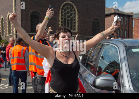Worcester, United Kingdom. 1 September 2018. The English Defence League (EDL) held a national demonstration in the West Midlands town of Worcester, approximately 200 people attended. A counter-protest was held a short distance away with approximately 500 people.  PICTURED: An EDL Supporter throws her arms up at counter-protesters in Worcester town centre. Credit: Peter Manning/Alamy Live News - Stock Image