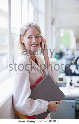 Smiling businesswoman holding folders and talking on cell phone in office - Stock Image