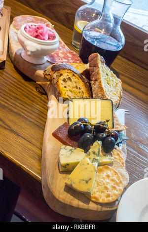Cheese plate selection with bread, sausage and red wine, Pig & Whistle  bistro charcuterie, Beverley, East Riding, Yorkshire, England - Stock Image