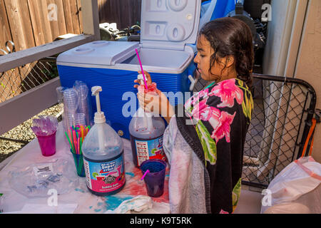 Hispanic girl, young girl, girl, making cherry flavored snow cone, pool party, Castro Valley, Alameda County, California, - Stock Image