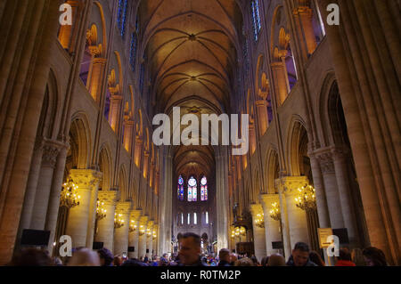PARIS, FRANCE - OCTOBER 27 2018: People inside the famous Notre Dame de Paris, Gothic Interior of the Cathedral crowded with visitors - Stock Image
