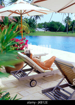 Woman sunbathing by pool at the Cap Est Lagoon Resort and Spa. Le Francois, Martinique. - Stock Image