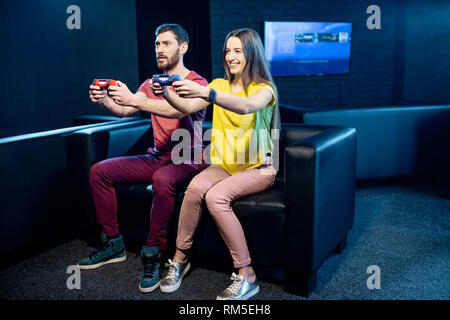Young couple playing video games with gaming console sitting on the couch in the dark room of the playing club - Stock Image