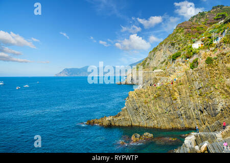 The rugged granite coastline of Cinque Terre at the village of Riomaggiore, Italy on the Ligurian Sea - Stock Image