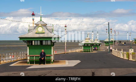 Blackpool, England, UK - August 1, 2015: A man sits on a bench in a traditional beach shelter on the Promenade in Blackpool. - Stock Image