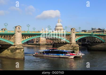 Thames Clipper river bus passes under Southwark Bridge London - Stock Image