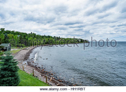 Canada geese swim in the waters of Lake Superior with the North Shore Commercial Fishing Museum, Tofte, MN, visible - Stock Image