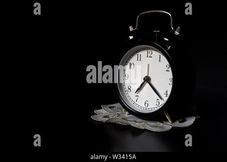 Classic mechanical alarm clock on dark background. Low key - Stock Image