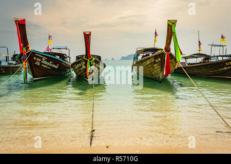 KRABI, THAILAND - NOVEMBER 2018: Thai traditional wooden boats with ribbon decoration at ocean shore near Krabi, Thailand - Stock Image