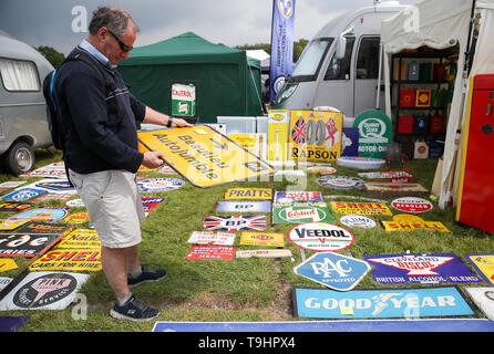 A person looks at road sign for sale at the Spring Autojumble at the National Motor Museum in Beaulieu, Hampshire. - Stock Image