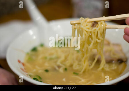 Japanese Ramen noodles being eaten with chopsticks. Taken in a restaurant in Osaka. - Stock Image