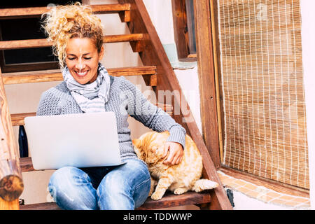 Cheerful pretty middle age woman work with laptop computer outdoor at home with nice cat near her - leisure technology activity and alternative office - Stock Image