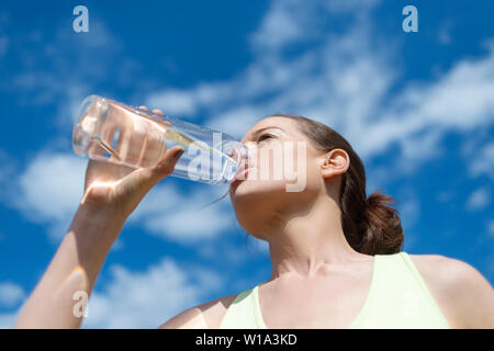 woman drinking from a reusable glass water bottle - Stock Image