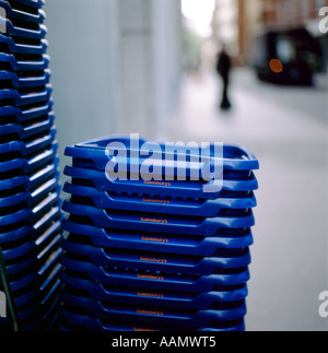 A stack of Sainsbury's shopping baskets outside the grocery  supermarket store in the City of London England UK  KATHY DEWITT - Stock Image