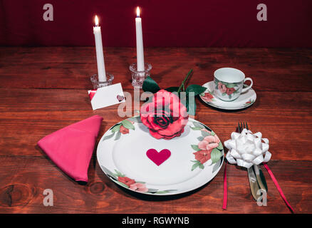 Floral pattern fine china dinnerware with matching plate, cup and saucer. pink rose, pink napkin, silverware, white candles and card - Stock Image