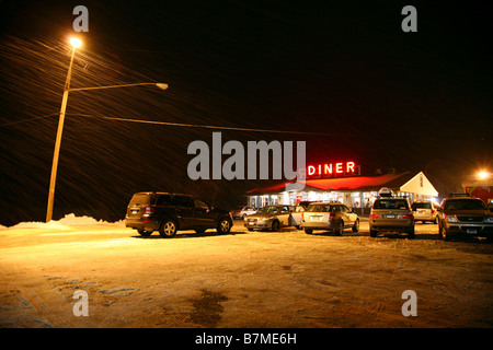 Diner illuminated at night in a snowstorm, Chatham, NY, USA - Stock Image