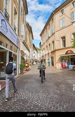 Tournon sur Rhone, Ardeche, Rhone Alps, France a man riding a bike and a man walking through the town centre - Stock Image