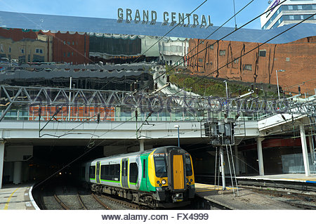 A train leaves Birmingham New Street railway station, with the exterior mirrors of the Grand Central shopping centre - Stock Image