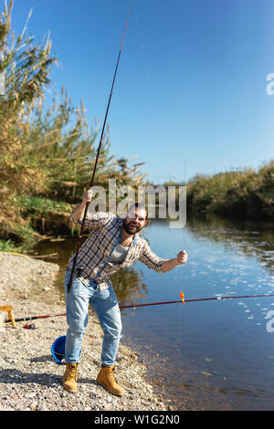 Adult man standing near river and pulling fish expressing emotions of dedication - Stock Image