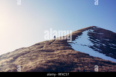 One Man hiker hiking alone climbing down a steep mountain path in winter. Taken from distance. Matte high contrast effect - Stock Image