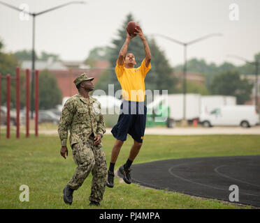 180825-N-BM202-1148 GREAT LAKES, Ill. (Aug. 25, 2018) Seaman Recruit Joan Beatos catches a football during a Recruit Training Command (RTC) Command Managed Equal Opportunity (CMEO) Women's Equality Celebration Festival at Constitution Field at Naval Station Great Lakes. More than 30,000 recruits graduate annually from the Navy's only boot camp. (U.S. Navy photo by Mass Communication Specialist 2nd Class Camilo Fernan/Released) - Stock Image