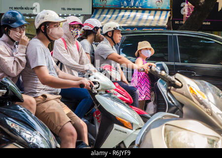 Hanoi, Vietnam - CIRCA October 2015: drivers in helmets, little girl in funny cap, pink dress and protective smog masks, due to air pollution. - Stock Image