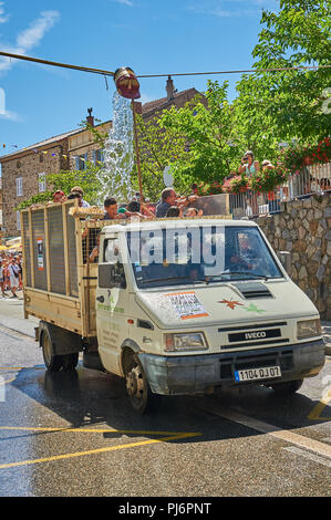 Saint Felicien and a white open back van passing under a water bucket as part of the festival of the goat and cheese - Stock Image