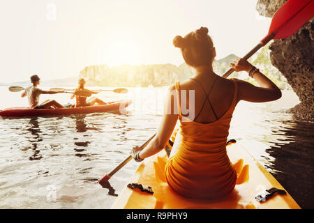 Slim lady walks by kayak at sea bay. Kayaking or canoeing concept with friends - Stock Image