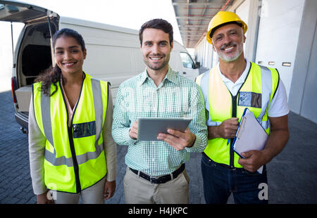 Manager and warehouse workers standing with digital tablet and clipboard - Stock Image