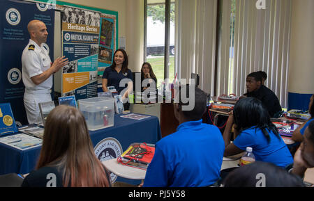 180827-N-RJ834-113 CLEVELAND (Aug. 27, 2018) Lt. Damien Horvath, from Bay Village, Ohio, attached to Navy Operational Support Unit in Tampa, Fla., speaks to students from Horizon Science Academy about what it takes to be an officer in the Navy during Cleveland Navy Week. The Navy Office of Community Outreach uses the Navy Week program to bring Navy Sailors, equipment and displays to approximately 14 American cities each year for a week-long schedule of outreach engagements designed for Americans to experience firsthand how the U.S. Navy is the Navy the nation needs. (U.S. Navy photo by Mass Co - Stock Image