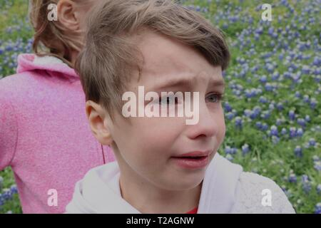 Portrait of a child in a field of wildflowers with a tear running down her cheek seemingly upset with her sister - Stock Image