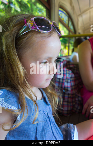 Young 4 year old girl daydreaming on a train carriage. - Stock Image