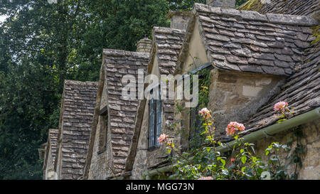 Bibury village's slate roofed row of dormers poke out of their Jacobean architecture - Stock Image