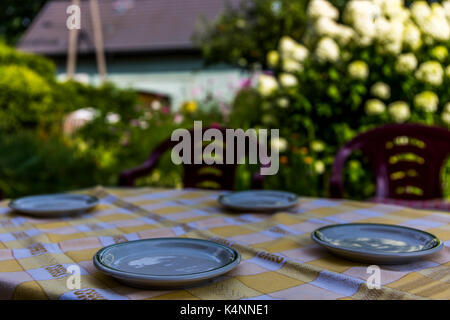 Small plates on a table  with garden in the background. - Stock Image