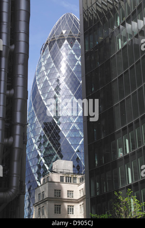 Swiss Re Tower viewed between Lloyds Building and Willis Building London - Stock Image