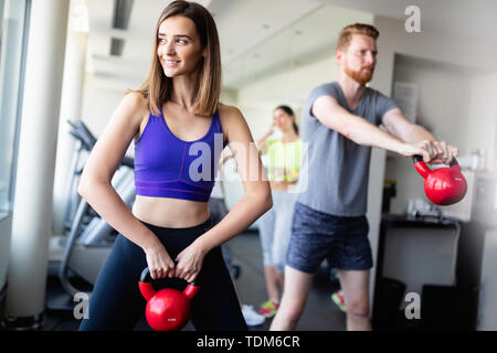 Group having functional fitness training with kettlebell in sport gym - Stock Image