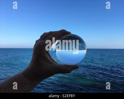 Creative photography. Seascape through a crystal ball, horizon, sea and sky inverted - Stock Image