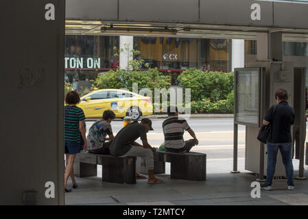 People wait at a bus stop in central Singapore - Stock Image