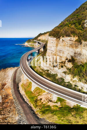Scenic Grand Pacific drive highway passing Sea Cliff Bridge around steep sandstone cliff on Pacific coast of Australia - aerial vertical view over the - Stock Image